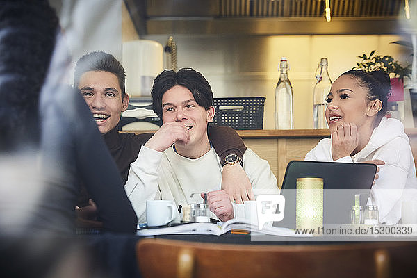 Smiling male and female teenage friends sitting at table in restaurant