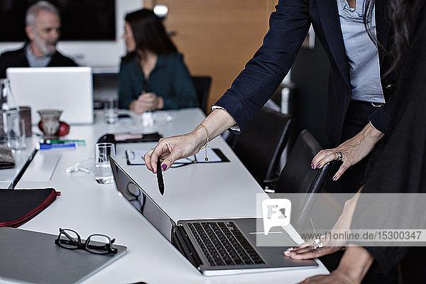 Ein Teil der Geschäftsfrauen diskutiert am Laptop mit Kollegen  die im Hintergrund im Büro arbeiten