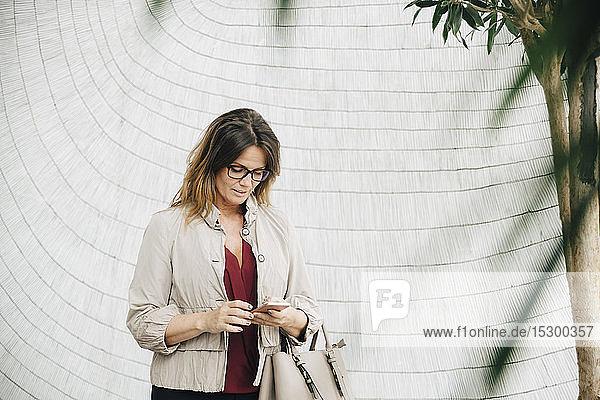 Geschäftsfrau benutzt Smartphone  während sie im Büro an der Wand steht Geschäftsfrau benutzt Smartphone, während sie im Büro an der Wand steht