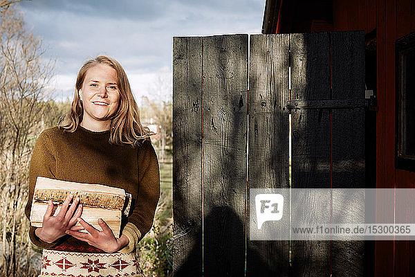 Porträt einer lächelnden jungen Frau  die Brennholz hält  während sie vor der Hütte steht
