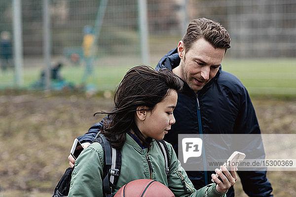 Sohn zeigt dem Vater sein Smartphone  während er am Sportgericht steht