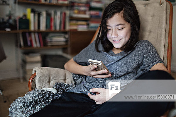 Smiling boy using social media on smart phone while sitting at home