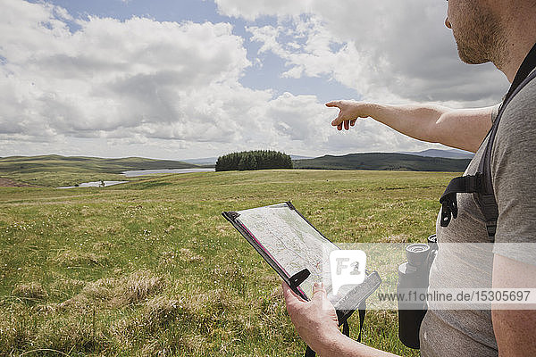 Man readinga map looking at view  Scotland  UK
