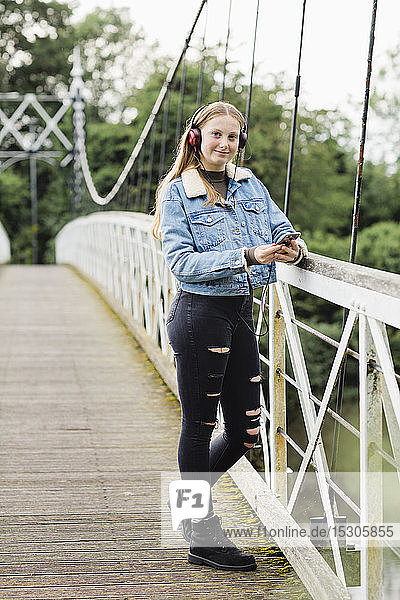 Teenage girl using smartphone and listening music on a bridge