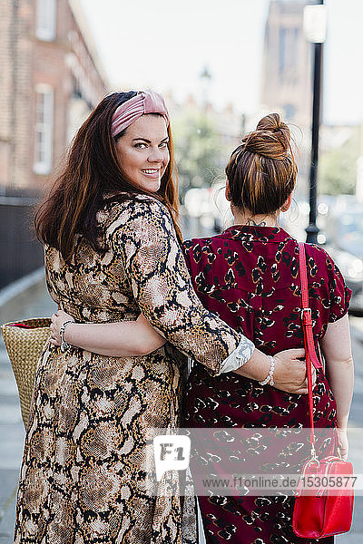 Back view of friends walking arm in arm on pavement  Liverpool  UK