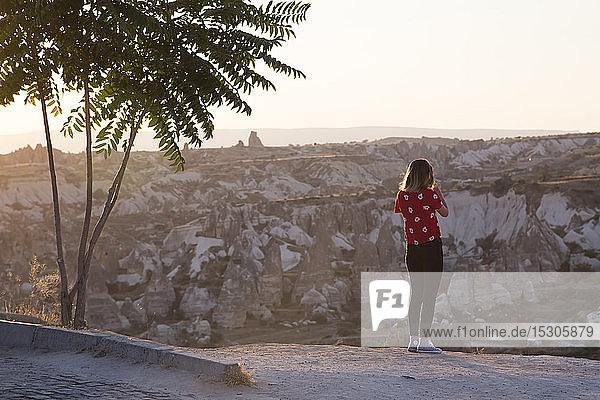 Woman taking a photo of rocky landscape at dusk  Goreme  Cappadocia  Turkey