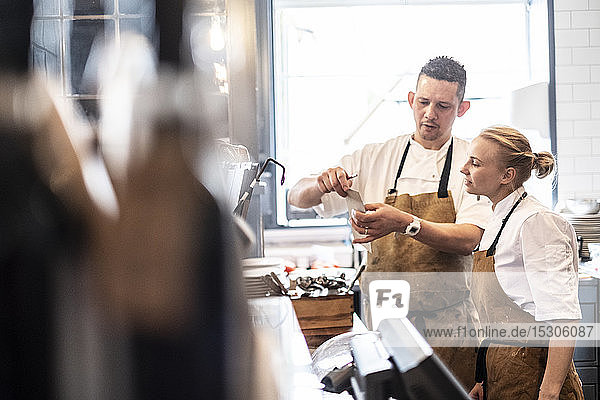 Male and female chef wearing brown aprons standing at a counter  checking an order.