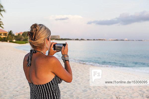 Erwachsene Frau  die mit einem Smartphone fotografiert