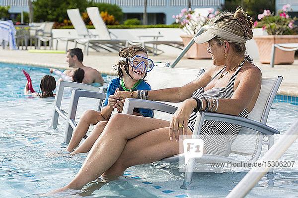 Mutter und ihr 5-jähriger Sohn beim Gespräch am Pool