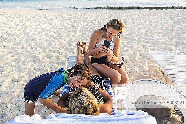 Mutter und ihre Kinder genießen den Strand bei Sonnenuntergang