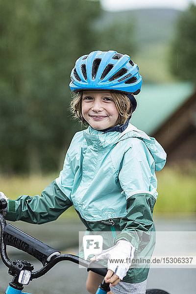 Porträt eines 5 Jahre alten Jungen in Regenjacke  der sich auf seinem Fahrrad abstützt