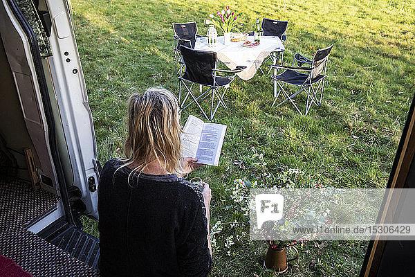 Hochwinkel-Rückansicht einer Frau  die in der Tür eines auf einer Wiese geparkten Wohnmobils sitzt und ein Buch liest.