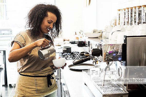 Woman barista preparing a cup of coffee in a coffee shop.