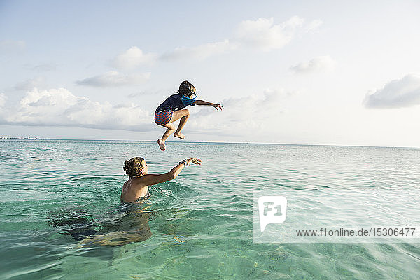 5 year old son on mother's shoulders leaping into the ocean at sunset