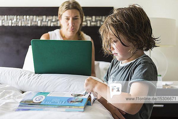 5 Jahre alter Junge betrachtet Buch im Hotelzimmer  während die Mutter am Laptop arbeitet