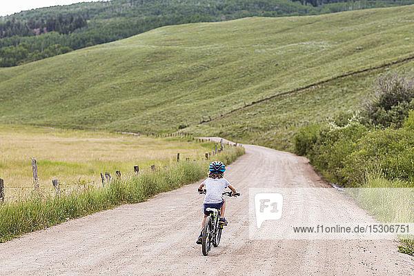 Rückansicht eines 5 Jahre alten Jungen  der auf einer Landstraße Fahrrad fährt