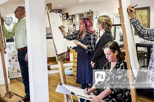 Gruppe von Künstlern  die an Staffeleien stehen und sitzen und zeichnen.