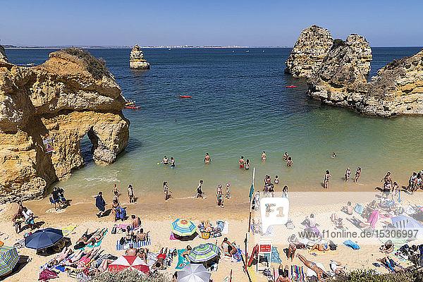 Tourists sunbathing and swimming on sunny  summer beach  Lagos  Algarve  Portugal