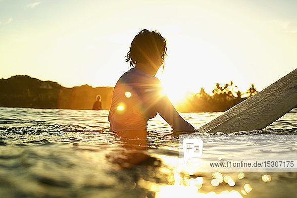 Female surfer on surfboard on sunny ocean at sunrise  Sayulita  Nayarit  Mexico
