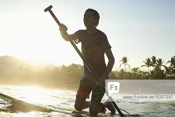 Boy kneeling on paddle board on sunny sunset ocean