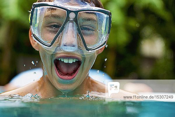Portrait exuberant boy in swimming goggles swimming