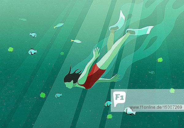 Frau schwimmt unter Wasser im Meer  umgeben von Fischen
