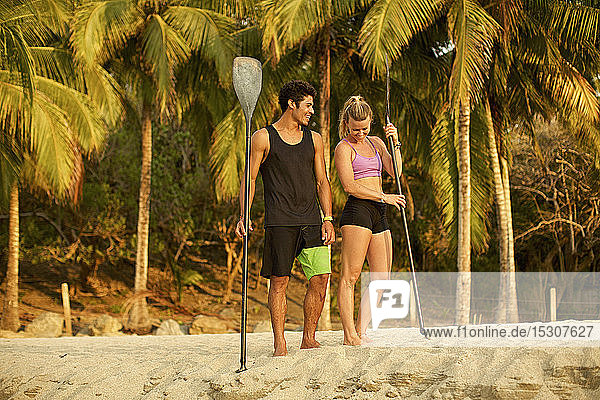 Young couple with oars on sunny  tropical beach