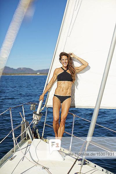 Portrait confident woman in bikini on sunny sailboat