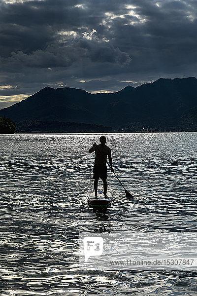 Silhouette Mann beim Paddeln auf einem sonnigen  idyllischen See  Walchensee  Bayern  Deutschland