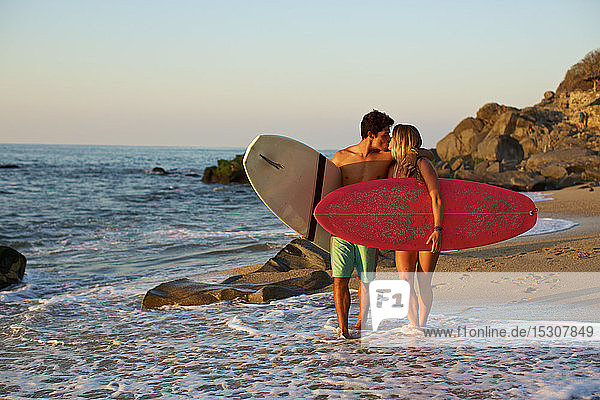 Young  affectionate couple with surfboards walking on sunny ocean beach  Sayulita  Nayarit  Mexico