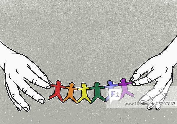 Hände halten LGBTQI-Regenbogen-Papierkette
