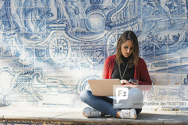 Woman using laptop and smart phone against mosaic wall