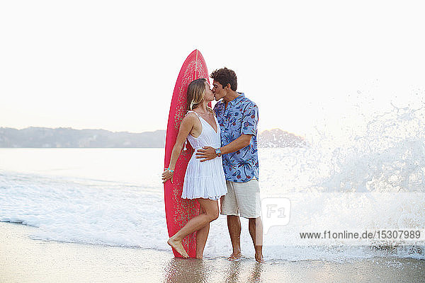 Affectionate couple with surfboard kissing on ocean beach  Sayulita  Nayarit  Mexico
