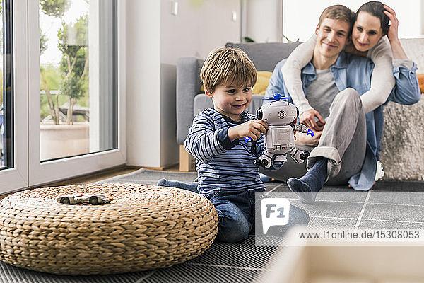 Eltern beobachten Sohn  spielen mit Spielzeugroboter