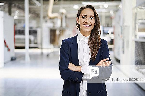 Porträt einer lächelnden Geschäftsfrau in einer Fabrik