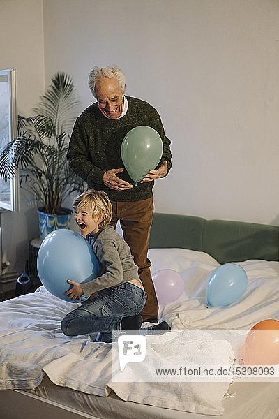 Glücklicher Großvater und Enkel spielen zu Hause mit Luftballons auf dem Bett