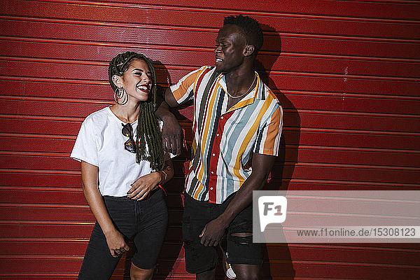 Glückliches junges Paar steht nachts am roten Rolltor