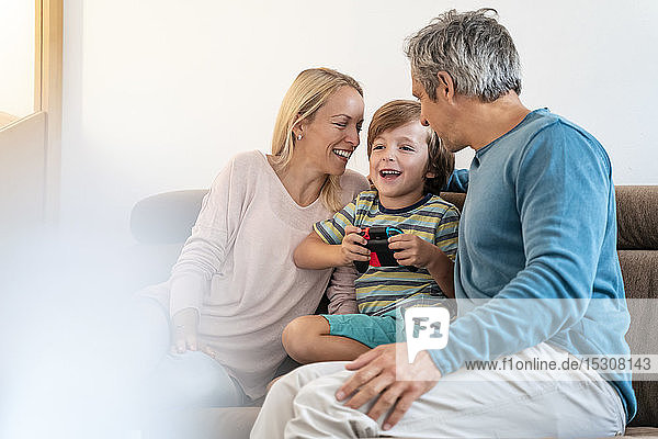 Happy parents with son playing video game on couch at home