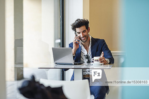 Smiling businessman using laptop and smartphone in an urban cafe