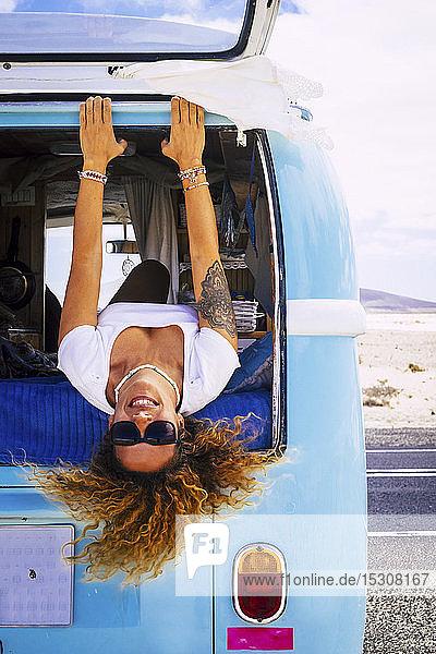 Frau mit Sonnenbrille liegt im Lieferwagen und schaut in die Kamera