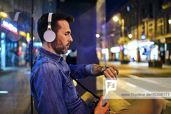 Serious man with wireless headphones waiting for night bus in the city and checking the time