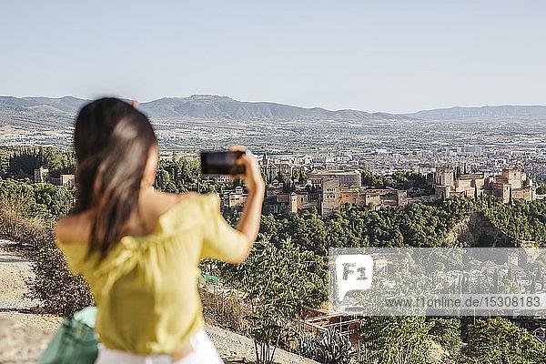 Junge Frau macht ein Handyfoto in der Alhambra,  Granada,  Spanien