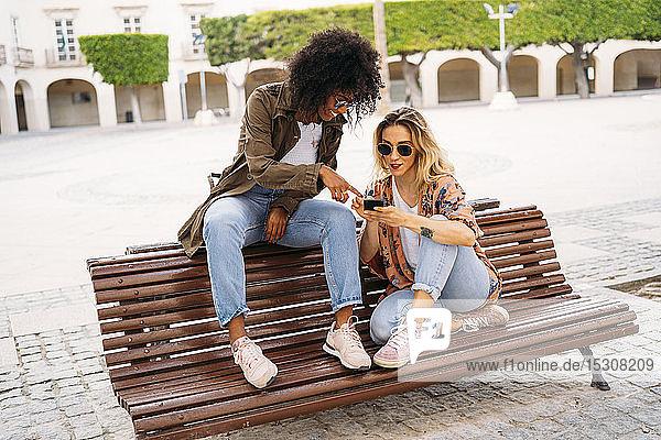 Multikulturelle glückliche Frauen  die sich unterhalten und ein Smartphone benutzen  auf einer Bank sitzend