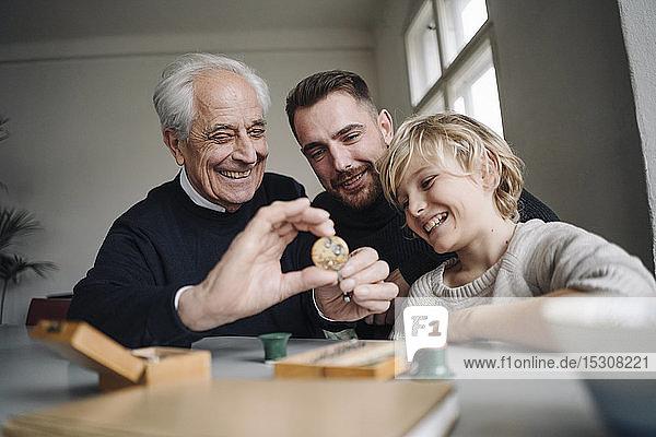Glücklicher Uhrmacher zeigt einem jungen Mann und Jungen ein Uhrwerk
