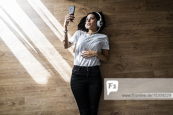 Young woman lying on the floor with smartphone and headphones