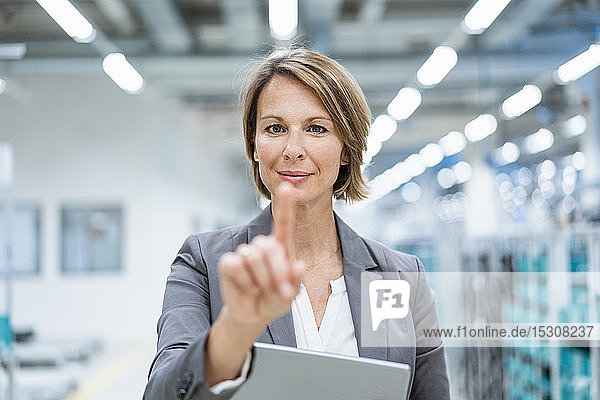 Portrait of businesswoman with tablet in a modern factory touching virtual screen