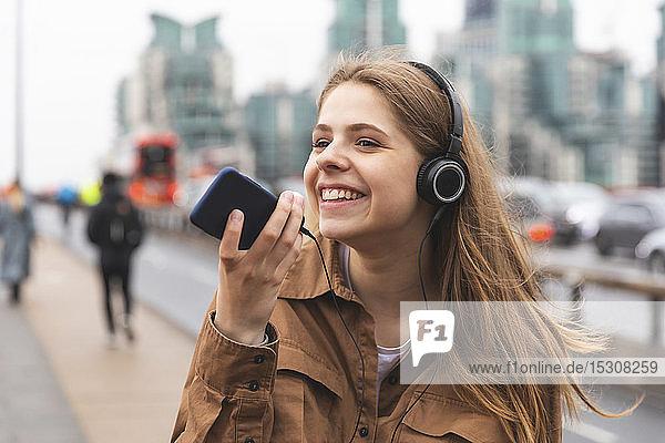 Glückliche junge Frau mit Kopfhörern und Handy in der Stadt  London  UK