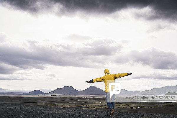 Erwachsener Mann steht mit ausgestreckten Armen im Hochlandgebiet von Island