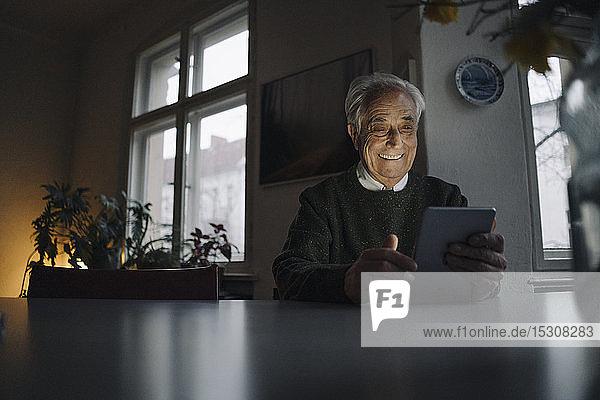 Lächelnder älterer Mann benutzt Tablette zu Hause