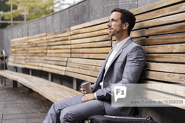 Entspannter Geschäftsmann sitzt auf Holzbank in der Stadt